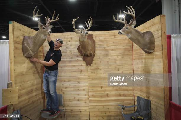 Aaron Quillan a hunting outfitter sets up his Monarch Rivers booth before the start of the 146th NRA Annual Meetings Exhibits on April 27 2017 in...