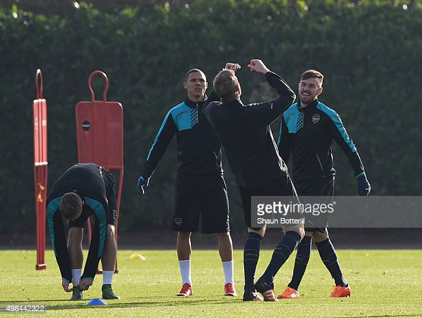 Aaron Ramsey and Kieran Gibbs of Arseanl share a joke with teammate Per Mertesacker during a training session at London Colney on November 23 2015 in...