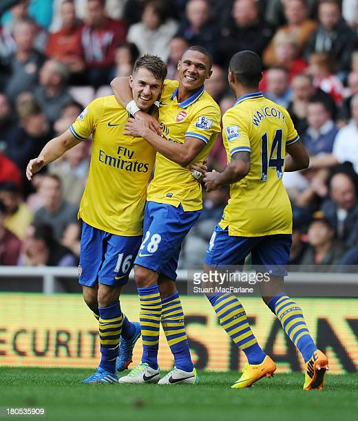 Aaron Ramsey celebrates scoring the 3rd Arsenal goal with Kieran Gibbs and Theo Walcott during the match at Stadium of Light on September 14 2013 in...