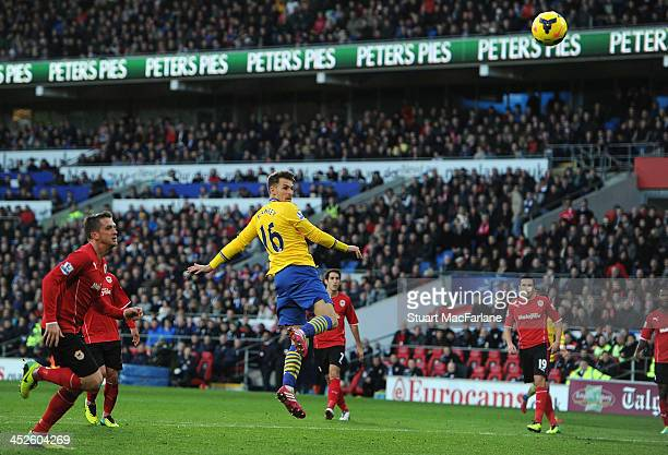 Aaron Ramsey heads past Cardiff goalkeeper David Marshall to score for Arsenal at Cardiff City Stadium on November 30 2013 in Cardiff Wales
