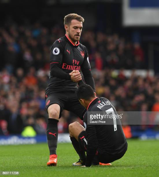 Aaron Ramsey helps up Alexis Sanchez of Arsenal during the Premier League match between Everton and Arsenal at Goodison Park on October 22 2017 in...