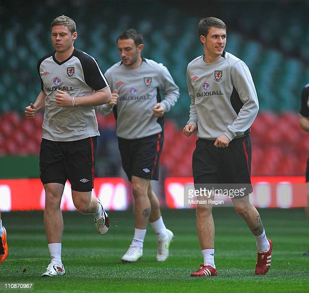 Aaron Ramsey looks on as he warms up with team mate Chris Gunter during the Wales training session ahead of their UEFA EURO 2012 qualifier against...