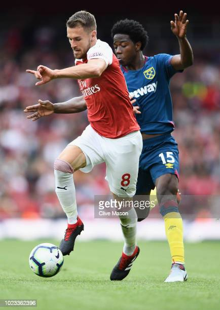 Aaron Ramsey of Arsenal and Carlos Sanchez of West Ham battle for the ball during the Premier League match between Arsenal FC and West Ham United at...