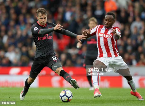 Aaron Ramsey of Arsenal and Saido Berahino of Stoke City battle for possession during the Premier League match between Stoke City and Arsenal at...