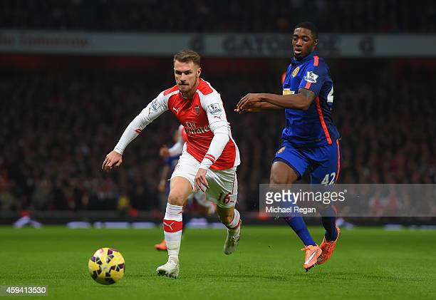 Aaron Ramsey of Arsenal and Tyler Blackett of Manchester United battle for the ball during the Barclays Premier League match between Arsenal and...