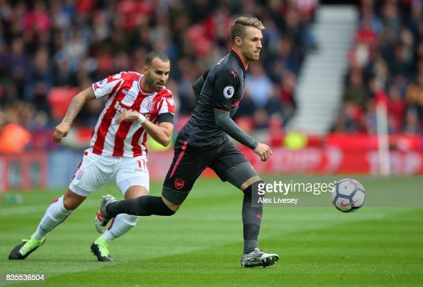 Aaron Ramsey of Arsenal attempts to get past Jese of Stoke City during the Premier League match between Stoke City and Arsenal at Bet365 Stadium on...