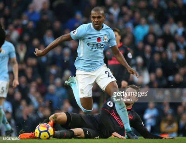 Aaron Ramsey of Arsenal attempts to tackles Fernandinho of Manchester City during the Premier League match between Manchester City and Arsenal at...