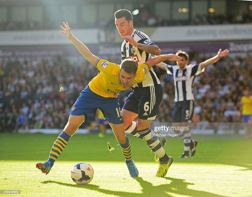Aaron Ramsey of Arsenal battles with Liam Ridgewell of West Bromwich Albion during the Barclays Premier League match between West Bromwich Albion and Arsenal at The Hawthorns on October 6, 2013 in West Bromwich, England.