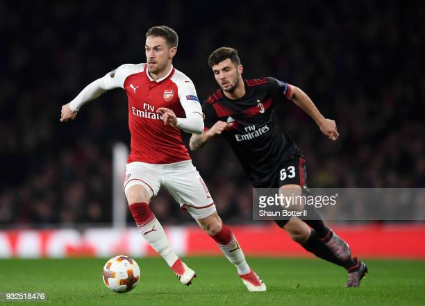 Aaron Ramsey of Arsenal breaks from Patrick Cutrone of AC Milan during the UEFA Europa League Round of 16 Second Leg match between Arsenal and AC...