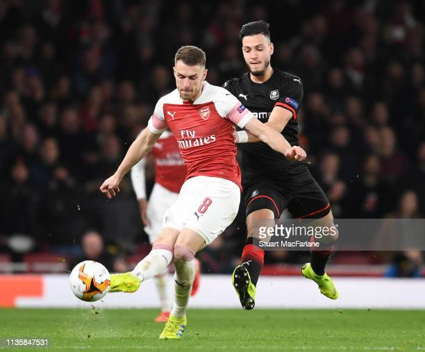 Aaron Ramsey of Arsenal breaks past Ramu Bensebaini of Rennes during the UEFA Europa League Round of 16 Second Leg match between Arsenal and Stade...