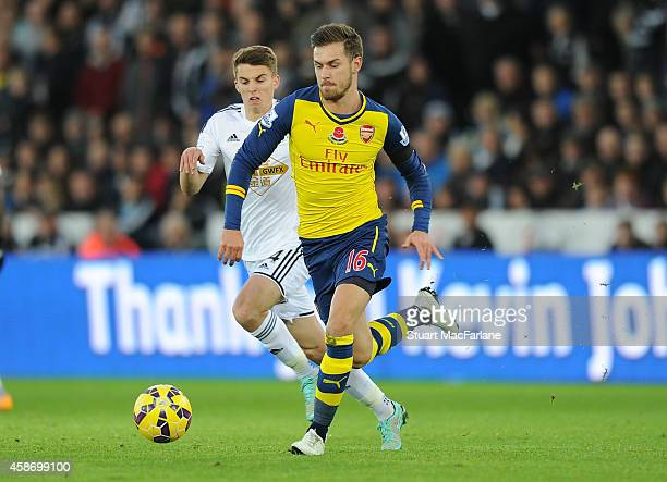 Aaron Ramsey of Arsenal breaks past Tom Carroll of Swansea during the Barclays Premier League match between Swansea City and Arsenal at Liberty...