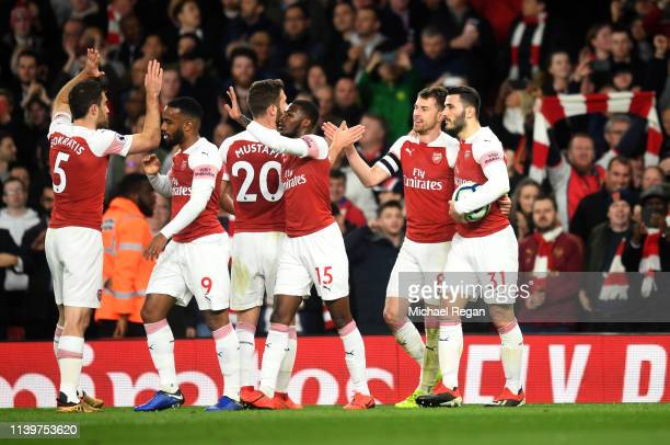 Aaron Ramsey of Arsenal celebrates as he scores his team's first goal with team mates during the Premier League match between Arsenal FC and...