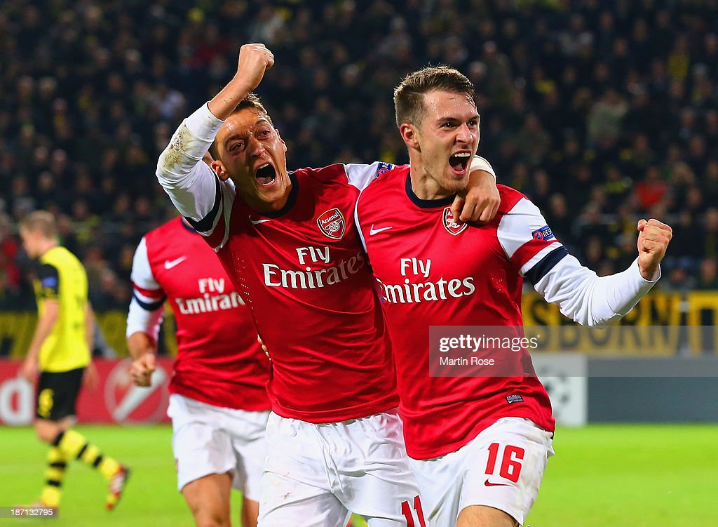 Aaron Ramsey of Arsenal (R) celebrates scoring their first goal with Mesut Oezil of Arsenal during the UEFA Champions League Group F match between Borussia Dortmund and Arsenal at Signal Iduna Park on November 6, 2013 in Dortmund, Germany.