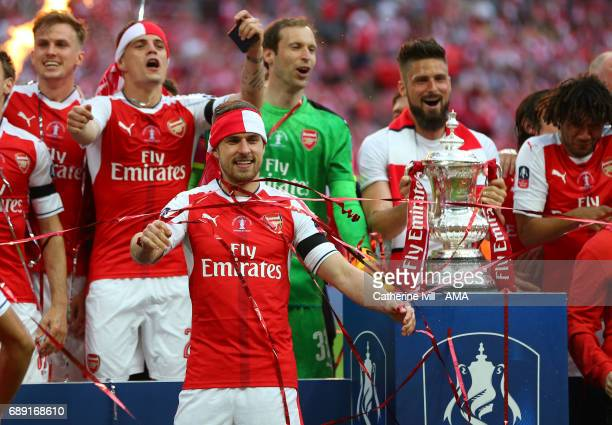 Aaron Ramsey of Arsenal celebrates with his team mates next to the trophy during the Emirates FA Cup Final match between Arsenal and Chelsea at...