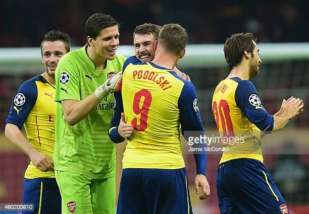 Aaron Ramsey of Arsenal celebrates with team mates Wojciech Szczesny and Lukas Podolski as he scores their third goal during the UEFA Champions...