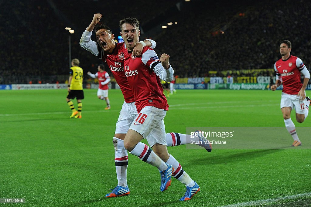 Aaron Ramsey (R) of Arsenal celebrates with team-mate Mesut Oezil after scoring the opening goal during the UEFA Champions League Group F match between Borussia Dortmund and Arsenal at Signal Iduna Park on November 6, 2013 in Dortmund, Germany.