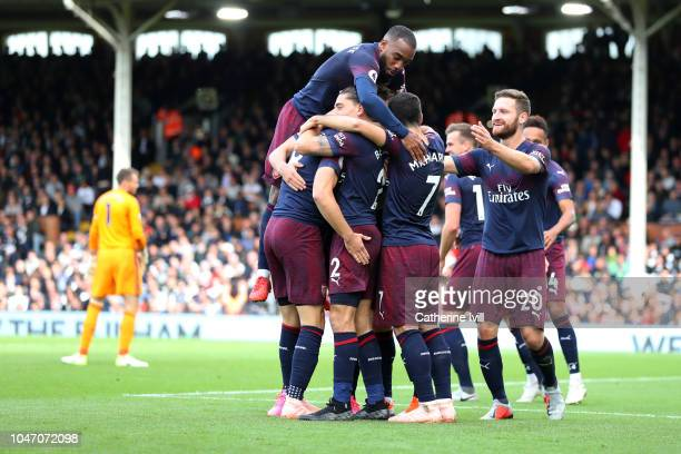 Aaron Ramsey of Arsenal celebrates with teammates after scoring his team's third goal during the Premier League match between Fulham FC and Arsenal...