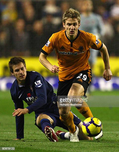 Aaron Ramsey of Arsenal challenges Kevin Doyle of Wolverhampton Wanderers during the Barclays Premier League match between Wolverhampton Wanderers...