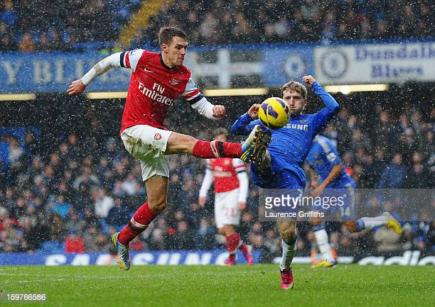 Aaron Ramsey of Arsenal challenges Marko Marin of Chelsea during the Barclays Premier League match between Chelsea and Arsenal at Stamford Bridge on...