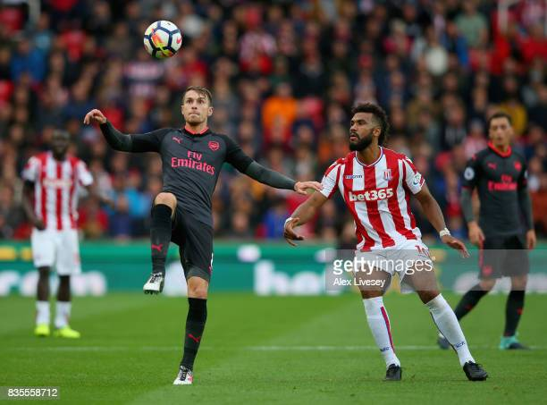 Aaron Ramsey of Arsenal clears the ball while under pressure from Maxim ChoupoMoting of Stoke City during the Premier League match between Stoke City...