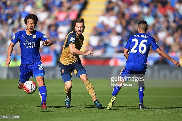 Aaron Ramsey of Arsenal competes against Shinji Okazaki and Riyad Mahrez of Leicester City during the Barclays Premier League match between Leicester...
