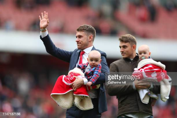 Aaron Ramsey of Arsenal holding one of his children acknowledges the crowd as he says farewell to the club following the Premier League match between...
