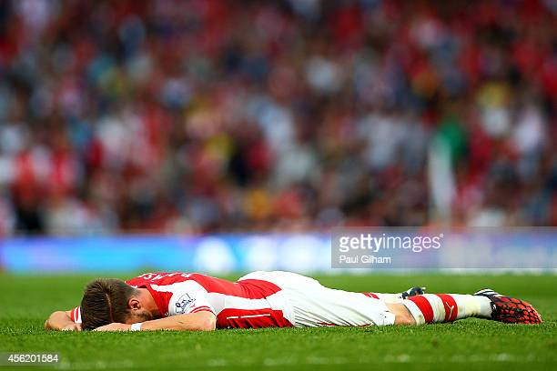 Aaron Ramsey of Arsenal holds his leg as he lies on the pitch after picking up an injury during the Barclays Premier League match between Arsenal and...