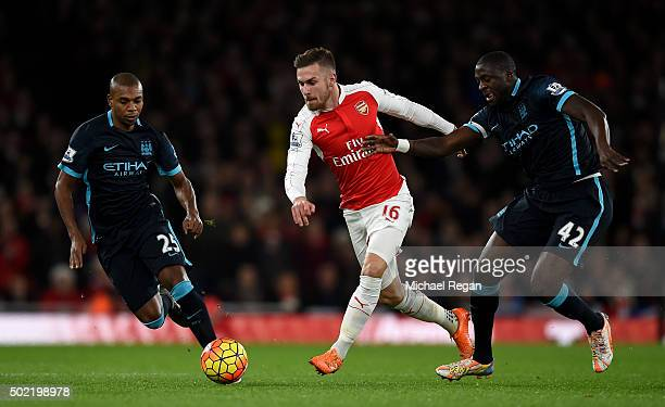 Aaron Ramsey of Arsenal holds off Fernandinho of Manchester City and Yaya Toure of Manchester City during the Barclays Premier League match between...