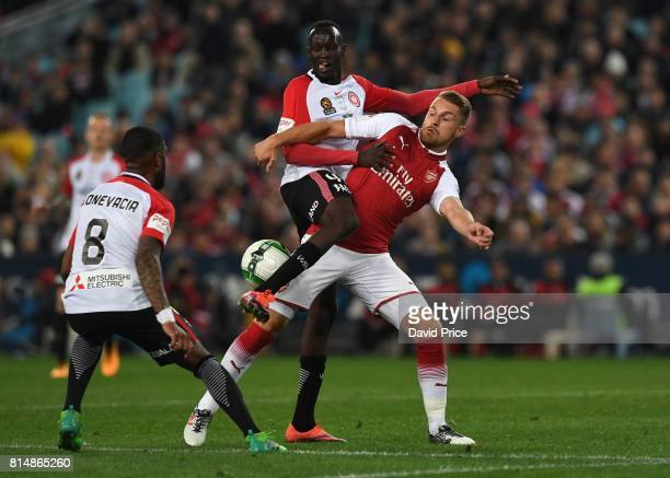Aaron Ramsey of Arsenal is challenged by Abraham Majok and Roly Bonevacia of Western Wanderers during the match between the Western Sydney Wanderers...