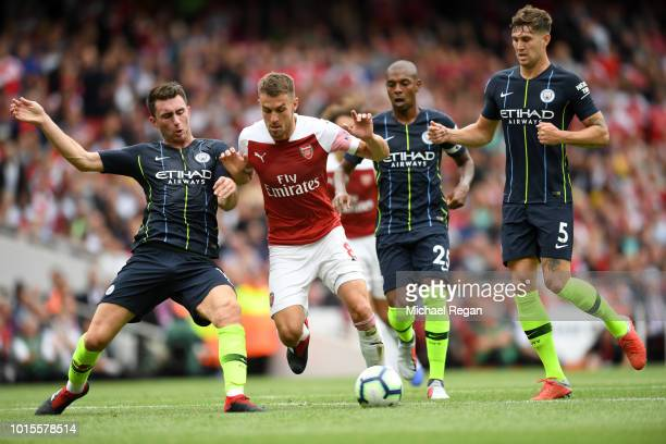 Aaron Ramsey of Arsenal is challenged by Aymeric Laporte of Manchester City during the Premier League match between Arsenal FC and Manchester City at...