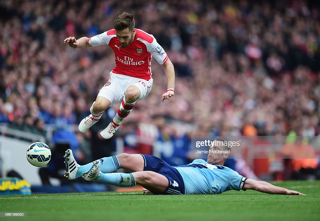 Aaron Ramsey of Arsenal is challenged by Kevin Nolan of West Ham United during the Barclays Premier League match between Arsenal and West Ham United at Emirates Stadium on March 14, 2015 in London, England.