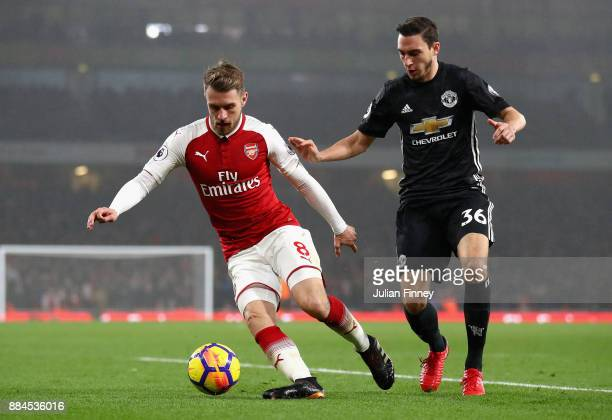 Aaron Ramsey of Arsenal is challenged by Matteo Darmian of Manchester United during the Premier League match between Arsenal and Manchester United at...