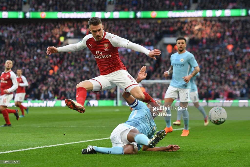 Aaron Ramsey of Arsenal is challenged by Vincent Kompany of Man City during the match between Arsenal and Manchester City at Wembley Stadium on February 25, 2018 in London, England.