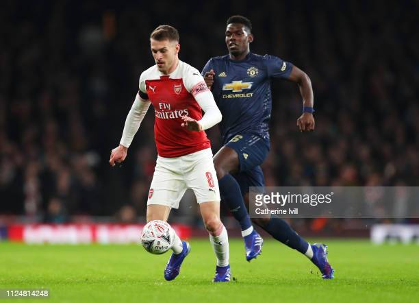 Aaron Ramsey of Arsenal is chased by Paul Pogba of Manchester United during the FA Cup Fourth Round match between Arsenal and Manchester United at...