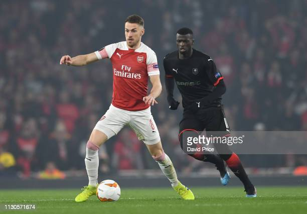 Aaron Ramsey of Arsenal is closed down by M'Baye Niang of Rennais during the UEFA Europa League Round of 16 Second Leg match between Arsenal and...