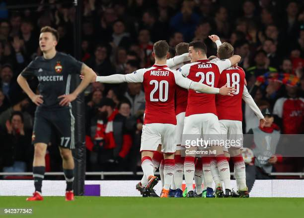 Aaron Ramsey of Arsenal is congratulated on scoring the opening goal during the UEFA Europa League quarter final leg one match between Arsenal FC and...