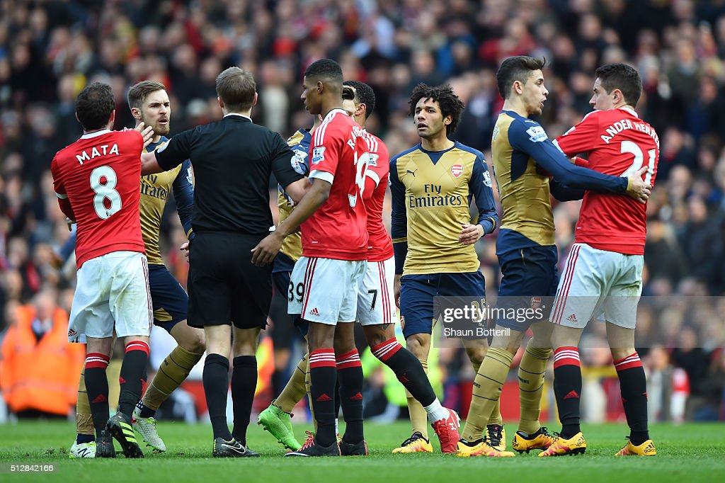 Aaron Ramsey of Arsenal is held back from Ander Herrera of Manchester United after a clash during the Barclays Premier League match between Manchester United and Arsenal at Old Trafford on February 28, 2016 in Manchester, England.
