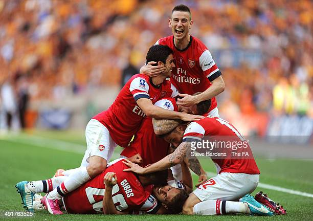 Aaron Ramsey of Arsenal is mobbed by his team mates after scoring their third goal in the extra time during the FA Cup with Budweiser Final match...