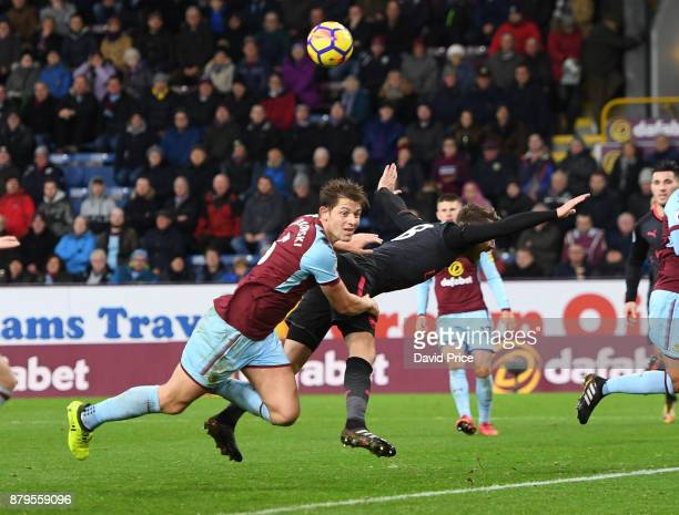 Aaron Ramsey of Arsenal is pushed in the back by James Tarkowski of Burnely during the Premier League match between Burnley and Arsenal at Turf Moor...
