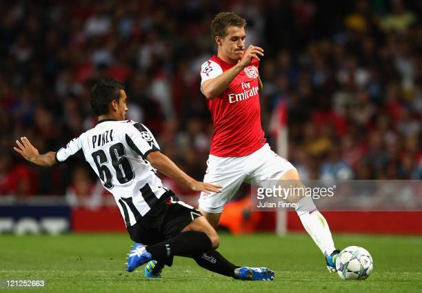Aaron Ramsey of Arsenal is tackled by Giampiero Pinzi of Udinese during the UEFA Champions League playoff first leg match between Arsenal and Udinese...