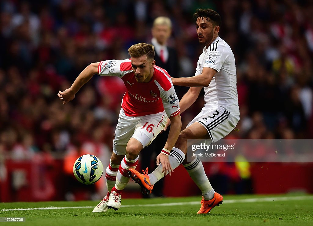 Aaron Ramsey of Arsenal is tackled by Neil Taylor of Swansea City during the Barclays Premier League match between Arsenal and Swansea City at Emirates Stadium on May 11, 2015 in London, England.