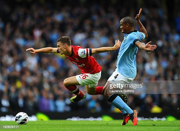Aaron Ramsey of Arsenal is tackled by Vincent Kompany of Manchester City during the Barclays Premier League match between Manchester City and Arsenal...