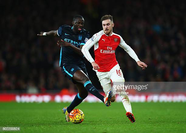 Aaron Ramsey of Arsenal is tackled by Yaya Toure of Manchester City during the Barclays Premier League match between Arsenal and Manchester City at...