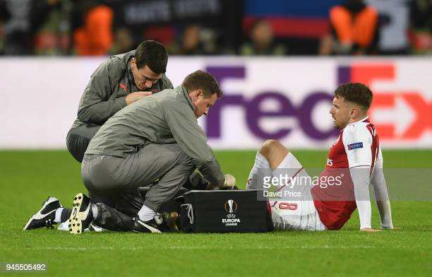 Aaron Ramsey of Arsenal is treated by physio Colin Lewin and Doctor Gary O'Driscoll during the UEFA Europa League quarter final leg two match between...