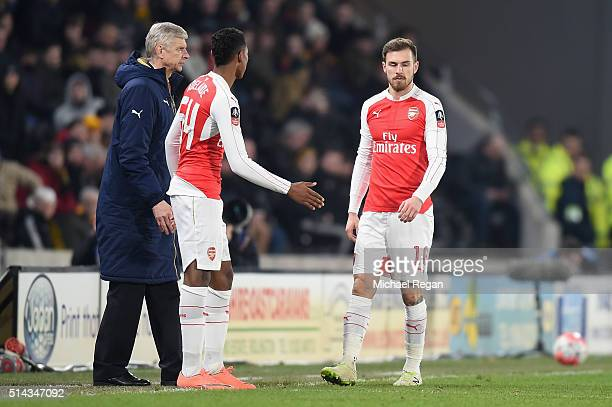 Aaron Ramsey of Arsenal leaves the field as Arsene Wenger Manager of Arsenal looks on during the Emirates FA Cup Fifth Round Replay match between...