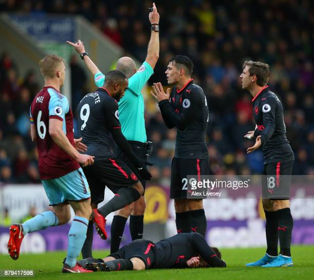 Aaron Ramsey of Arsenal lies injured as Alexandre Lacazette Granit Xhaka and Nacho Monreal react during the Premier League match between Burnley and...