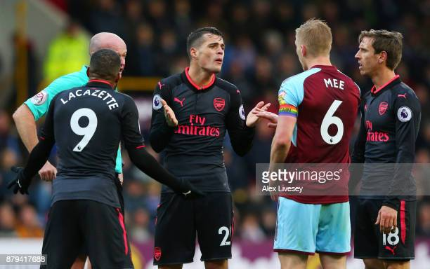 Aaron Ramsey of Arsenal lies injured as Alexandre Lacazette Granit Xhaka and Nacho Monreal react ands Ben Mee of Burnley looks on during the Premier...