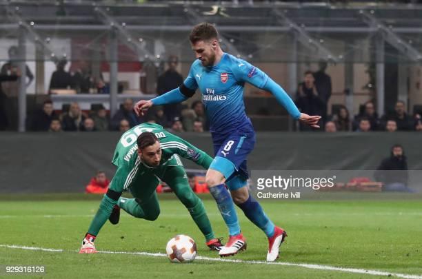 Aaron Ramsey of Arsenal rounds AC Milan goalkeeper Gianluigi Donnarumma to score during the UEFA Europa League Round of 16 match between AC Milan and...