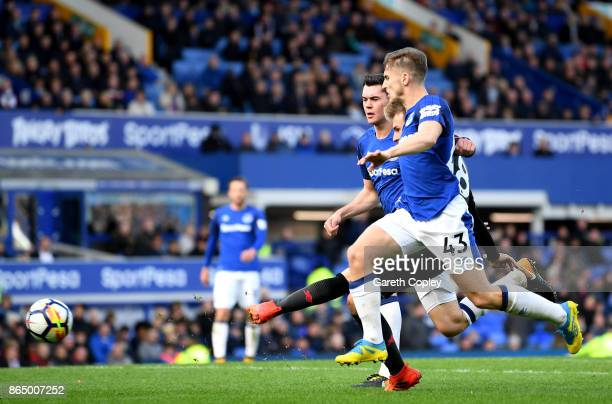 Aaron Ramsey of Arsenal scores his sides fourth goal while under pressure from Phil Jagielka of Everton and Jonjoe Kenny of Everton during the...