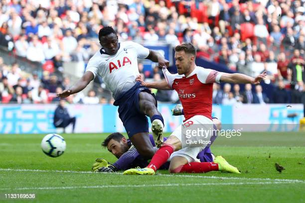 Aaron Ramsey of Arsenal scores his team's first goal as he is is challenged by Victor Wanyama of Tottenham Hotspur after taking the ball past Hugo...
